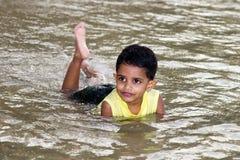 Nuoto del ragazzo nel fiume Fotografia Stock