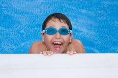 nuoto del ragazzo nel raggruppamento con gli occhiali di protezione e un grande g Immagine Stock