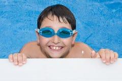 Nuoto del ragazzo nel raggruppamento con gli occhiali di protezione e un grande g Immagine Stock Libera da Diritti