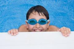 Nuoto del ragazzo nel raggruppamento con gli occhiali di protezione e un grande g Fotografie Stock Libere da Diritti