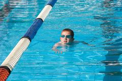 Nuoto del ragazzo in un raggruppamento fotografia stock