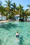 Nuoto dell'uomo sotto l'acqua in raggruppamento Immagine Stock