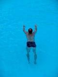 Nuoto dell'uomo in un raggruppamento Fotografia Stock Libera da Diritti
