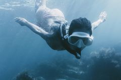 Nuoto della donna con la maschera e la presa d'aria immagine stock