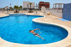 Nuoto della donna nella piscina blu un giorno soleggiato Fotografia Stock