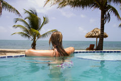 Nuoto della donna nello stagno di infinito accanto all'oceano Immagine Stock Libera da Diritti