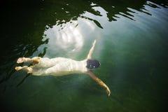 Nuoto della donna sotto l'acqua Fotografia Stock