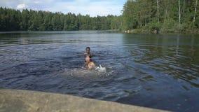 Nuoto della famiglia in un lago della foresta in Finlandia archivi video