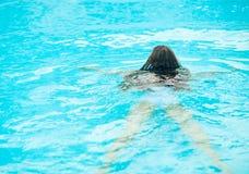 Nuoto della giovane donna nel raggruppamento. Retrovisione Immagini Stock