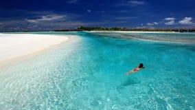 Nuoto della giovane donna nella laguna tropicale