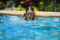 Nuoto della giovane donna in un raggruppamento Fotografia Stock Libera da Diritti