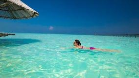 Nuoto della giovane donna in una laguna di corallo video d archivio