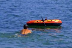 Nuoto della persona intorno alla barca Immagine Stock