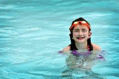 Nuoto della ragazza nello stagno con gli occhiali di protezione arancio Fotografia Stock Libera da Diritti