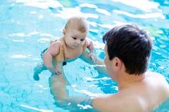 Nuoto di mezza età felice del padre con il bambino adorabile sveglio nella piscina Immagine Stock Libera da Diritti