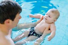 Nuoto di mezza età felice del padre con il bambino adorabile sveglio nella piscina Fotografie Stock Libere da Diritti