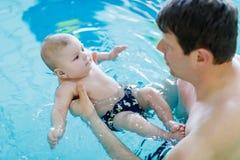 Nuoto di mezza età felice del padre con il bambino adorabile sveglio nella piscina Fotografia Stock Libera da Diritti