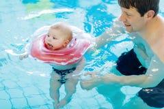 Nuoto di mezza età felice del padre con il bambino adorabile sveglio nella piscina Fotografie Stock