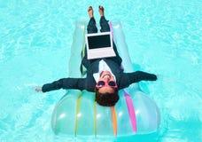 Nuoto felice della donna di affari sul lilo in stagno Immagini Stock