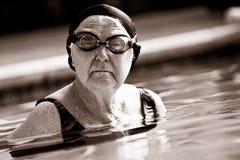 Nuoto maggiore della donna in un raggruppamento Immagini Stock