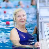 Nuoto senior della donna nello stagno Fotografia Stock