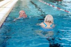 Nuoto senior delle coppie nello stagno Immagini Stock