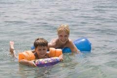 Nuoto sorridente della mamma e del ragazzo dentro Immagini Stock