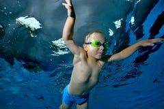 Nuoto subacqueo Un ragazzino sta nuotando underwater nello stagno su un fondo blu Ritratto Vista dal basso Foto subacquea fotografia stock libera da diritti