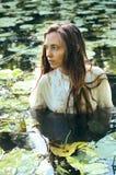 Nuoto tenero della giovane donna nello stagno fra le ninfee Immagini Stock