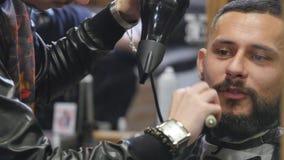 Nuova acconciatura Vista laterale di giovane uomo barbuto che ottiene governato al parrucchiere con il fon mentre sedendosi nella stock footage