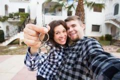 Nuova casa, bene immobile e concetto commovente - giovani chiavi divertenti di rappresentazioni delle coppie dalla nuova casa fotografia stock