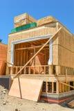 Nuova casa di famiglia in costruzione con le pile di bordi del legname 2x4 sulla cima fotografia stock libera da diritti