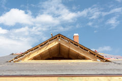Nuova casa di legno in costruzione Tetto con le assicelle dell'asfalto, il camino ed il materiale di isolamento fotografia stock