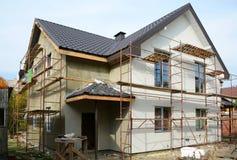 Nuova casa moderna della costruzione di casa Costruzione del tetto Camino del metallo Facciata isolata ed intonacata Tetto della  Immagine Stock
