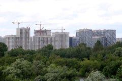 Nuova costruzione di edifici in nuovo distretto dopo il fiume sopra il cielo con le nuvole bianche nel giorno di estate Fotografia Stock