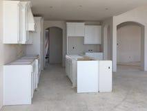Nuova cucina bianca con il contatore dell'isola in costruzione Immagini Stock