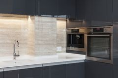 Nuova cucina moderna con costruito nel rubinetto di acqua del cromo e del forno Illuminazione di piano di lavoro del LED immagine stock