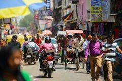 Nuova Delhi, India - 16 aprile 2016: Vista alla via ammucchiata con i negozi, gli hotel, il trasporto e la gente in bazar princip Fotografie Stock Libere da Diritti