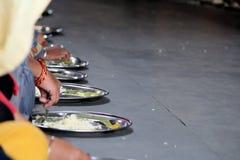 NUOVA DELHI, INDIA - 21 marzo 2019: i pellegrini mangiano i pasti liberi nel tempio dorato Gurudwara Bangla Sahib a Delhi fotografia stock