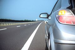 Nuova guida di veicoli velocemente su una strada in montagne Immagini Stock