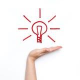 Nuova idea con la lampadina brillante sulla palma Immagine Stock