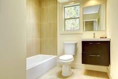Nuova stanza da bagno gialla moderna con le mattonelle beige. fotografia stock