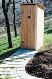 Nuova toilette di legno nel giardino - foro a forma di del cuore sulla porta fotografie stock libere da diritti