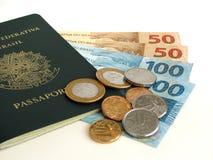 Nuova valuta brasiliana con il passaporto e le monete Fotografia Stock