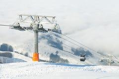 Nuove cabine di funivia che vanno su e giù le montagne ad un'area di località di soggiorno degli sport invernali un giorno solegg Immagine Stock