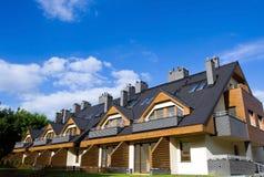 Nuove case sopra il cielo nuvoloso blu Immagine Stock Libera da Diritti