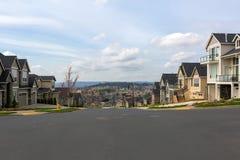 Nuove case su misura in via suburbana della vicinanza immagine stock