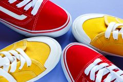 Nuove paia delle scarpe da tennis rosse e gialle su fondo viola Scarpe da tennis di stile di vita immagine stock