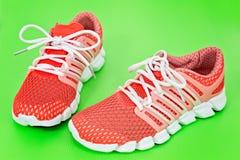 Nuove scarpe da corsa, scarpe da tennis o istruttori arancio e bianchi sul gree Fotografie Stock