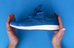 Nuove scarpe da tennis nelle mani immagine stock